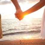 couple holding hands on the beach at sunset